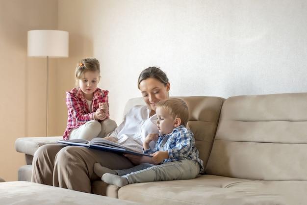 Jovem mãe lendo um livro para seus filhos pequenos