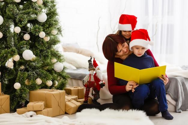 Jovem mãe lendo um livro para sua filha bonita e filho perto de árvore de natal