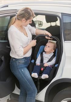 Jovem mãe levando seu bebê na cadeirinha para fora do carro
