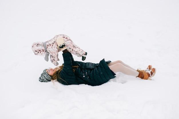 Jovem mãe linda brincando com a filha ao ar livre no inverno.