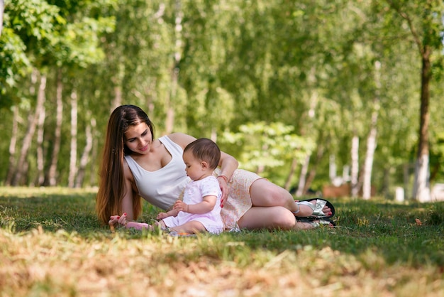 Jovem mãe linda brincando com um bebê na grama em um parque.