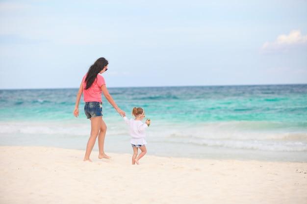 Jovem mãe linda e sua adorável filha correndo ao longo do mar