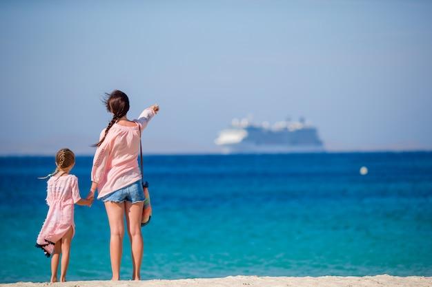 Jovem mãe linda e sua adorável filha pequena na praia tropical, olhando para o mar