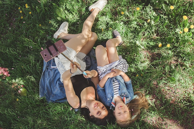 Jovem mãe linda e sua filha fazendo selfie no telefone móvel. mãe e sua filha se divertindo ao ar livre no parque. meninas fazendo foto no celular e sorrindo
