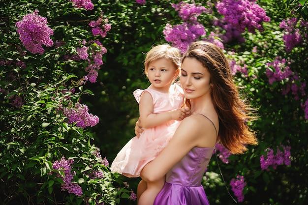 Jovem mãe linda mantém sua filha nos braços. conceito de dia das mães copie o espaço