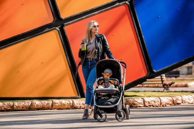 Jovem mãe linda passeios no parque com a criança no carrinho, bebe café