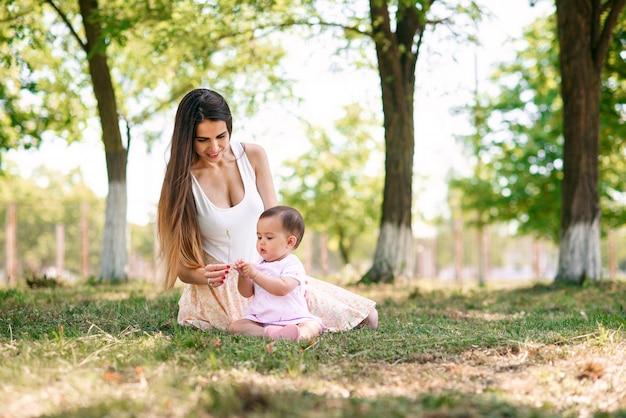 Jovem mãe linda senta-se com seu bebê na grama em um parque.