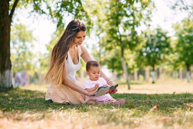 Jovem mãe linda sentada com seu bebê na grama em um parque e livro de leitura. mãe lê contos de fadas para sua filha ao ar livre.