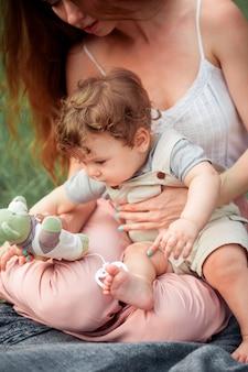 Jovem mãe linda sentada com seu filho pequeno