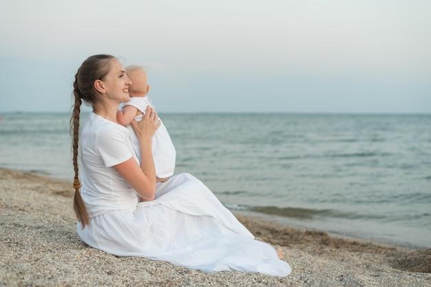 Jovem mãe linda sentada na praia e abraços bebê.