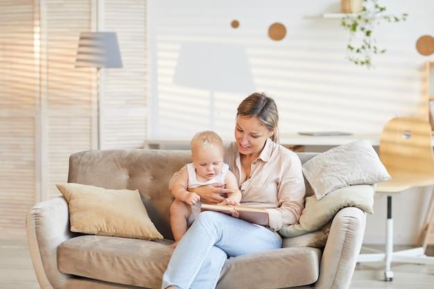 Jovem mãe moderna sentada no sofá da sala de estar com seu livro de leitura infantil curioso