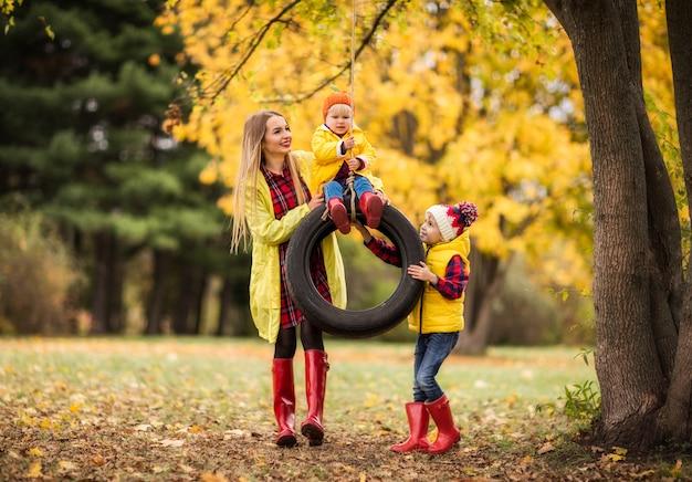Jovem mãe monta crianças em uma roda no parque outono