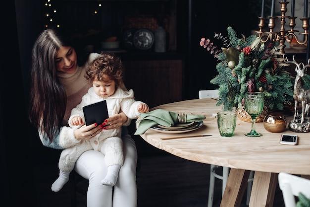 Jovem mãe mostra algo interessante para a filha antes do natal