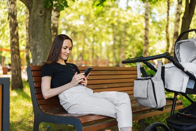 Jovem mãe, mulher com smartphone nas mãos, sentada no banco do parque ao lado do carrinho com o bebê