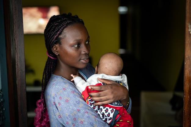 Jovem mãe negra segurando bebê