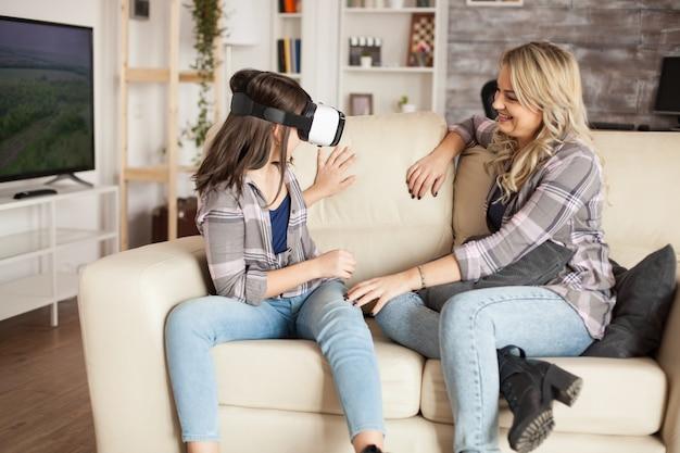 Jovem mãe olhando para sua filha se divertindo com fone de ouvido de realidade virtual. maternidade moderna.