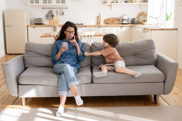 Jovem mãe ou babá usando smartphone pede a criança para parar de fumar criança perturba a mãe do telefone celular