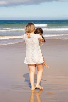 Jovem mãe passando tempo de lazer com a filha na praia, no mar, segurando a criança nos braços