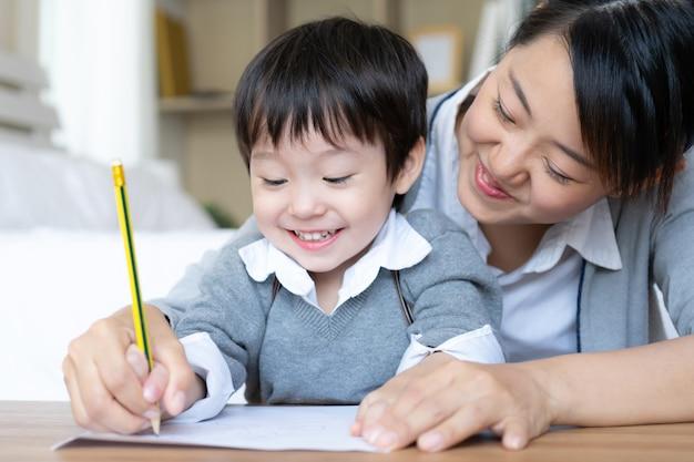 Jovem mãe pegou a mão do filho segurando um lápis para sarampo escrever em papel branco, pré-escola em casa