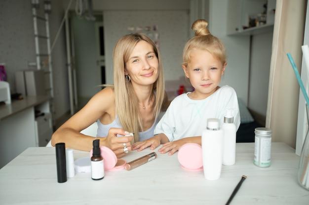Jovem mãe pinta as unhas de suas filhas