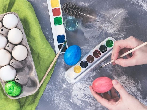 Jovem mãe pintando ovos de páscoa