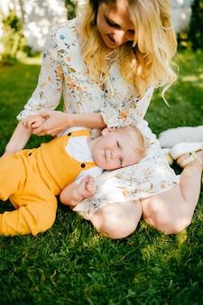 Jovem mãe posando com o sol na grama