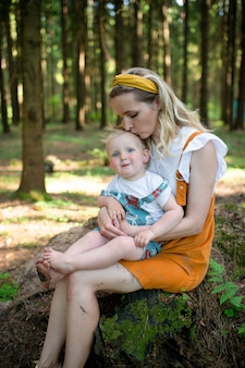 Jovem mãe posando com seu filho engraçado na floresta