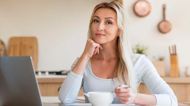 Jovem mãe posando enquanto trabalhava e tomando café da manhã em casa