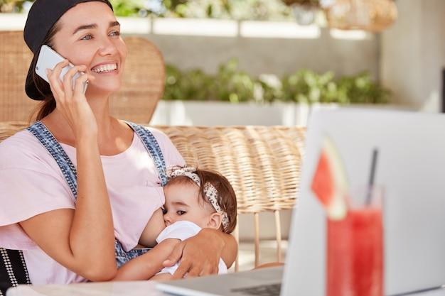 Jovem mãe positiva de olhos azuis dá leite materno ao seu bebê, fala com alguém pelo telefone celular, dá conselhos sobre como cuidar dos filhos