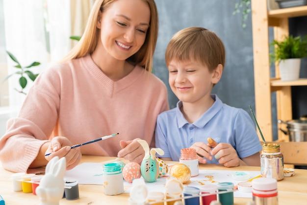 Jovem mãe positiva sentada à mesa fazendo desenho de coelho para ovos de páscoa com o filho