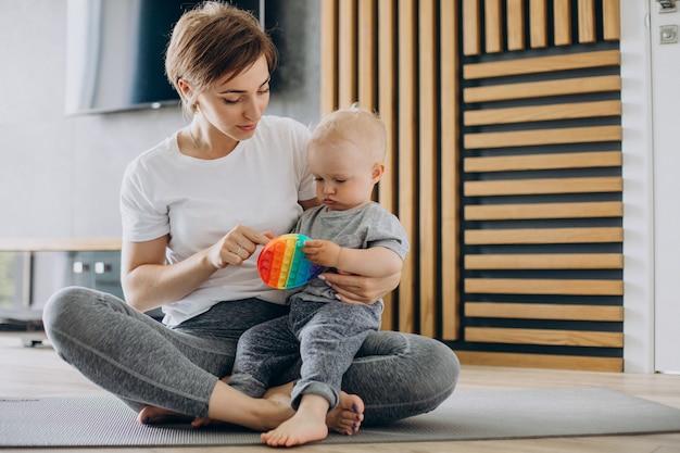 Jovem mãe praticando ioga com o filho pequeno no colchonete