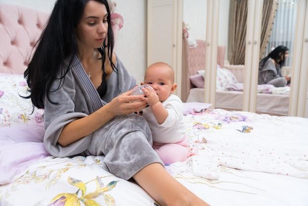Jovem mãe preparando uma mamadeira para sua filhinha enquanto elas relaxam juntas em uma cama refletida no espelho do guarda-roupa