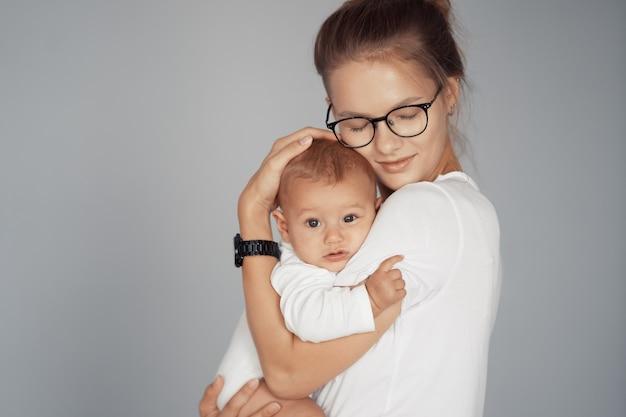 Jovem mãe se diverte com seu bebê em casa