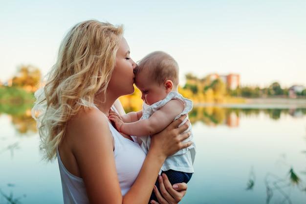 Jovem mãe segurando e beijando o bebê pelo rio de verão. mulher andando com criança ao pôr do sol