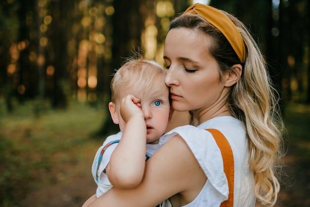 Jovem mãe segurando o filho na floresta