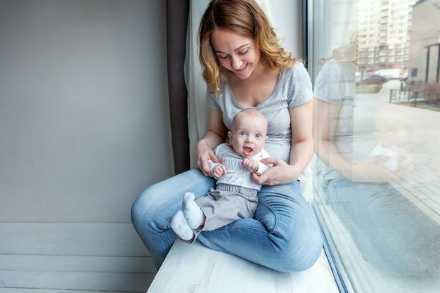 Jovem mãe segurando o filho recém-nascido. mulher e menino infantil relaxar e brincar no quarto perto da janela