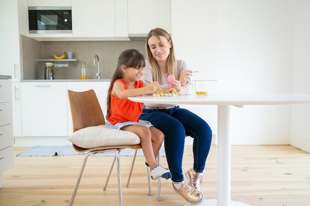 Jovem mãe segurando ovo de páscoa, sorrindo e mostrando a filha na cozinha.
