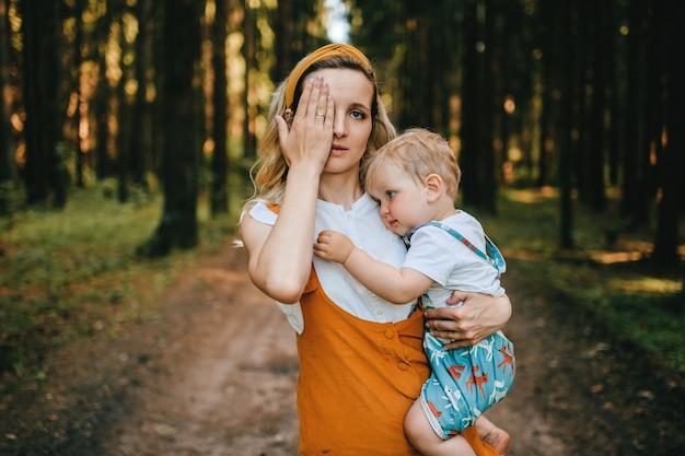 Jovem mãe segurando seu adorável filho na floresta