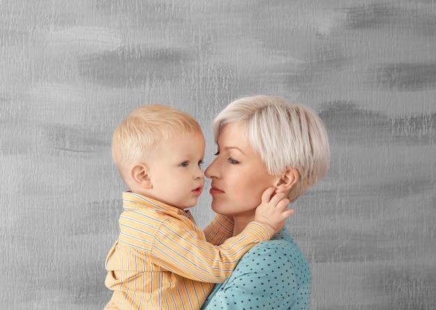 Jovem mãe segurando seu bebê na cama cinza