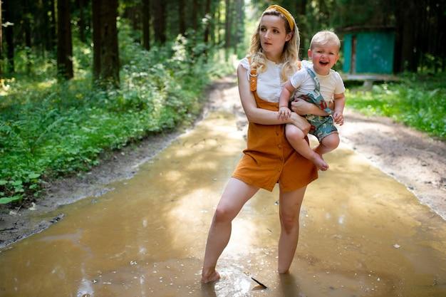 Jovem mãe segurando seu filho chorando e parada na poça na floresta