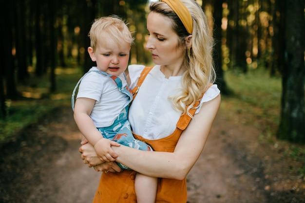 Jovem mãe segurando seu filho chorando na floresta
