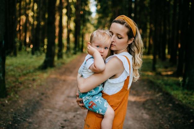 Jovem mãe segurando seu filho engraçado na floresta