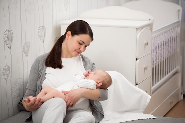 Jovem mãe segurando seu filho recém-nascido