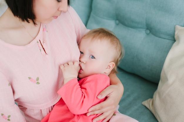 Jovem mãe senta-se no sofá no quarto e amamenta a filha