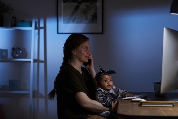 Jovem mãe sentada à mesa em frente ao monitor do computador com a criança ajoelhada e falando no celular em casa