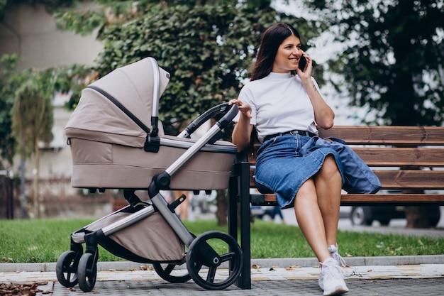Jovem mãe sentada no banco do parque com carrinho de bebê