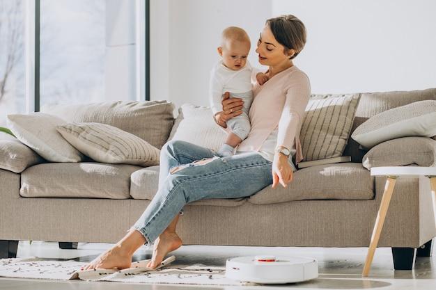 Jovem mãe sentada no sofá com o filho pequeno observando um robô aspirador de pó fazendo o trabalho doméstico