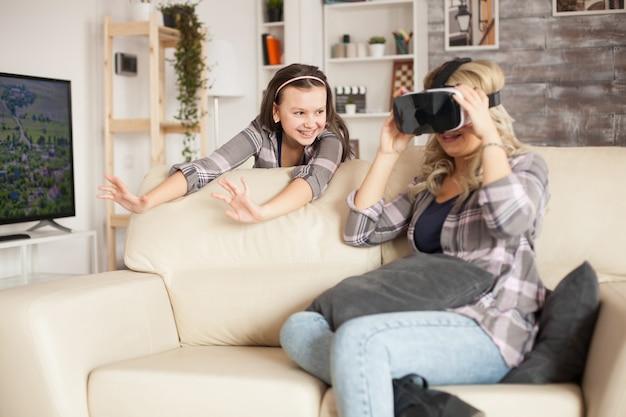 Jovem mãe sentada no sofá da sala de estar usando óculos de realidade virtual. filha alegre com aparelho.