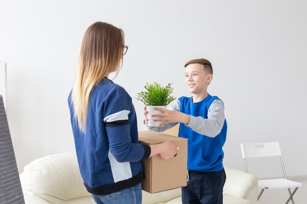 Jovem mãe solteira e um filho brincalhão segurando uma caixa com coisas e uma flor em um vaso na sala de estar de um apartamento novo. festa de inauguração e novo conceito de habitação.