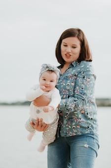 Jovem mãe sorridente com seu bebê na praia